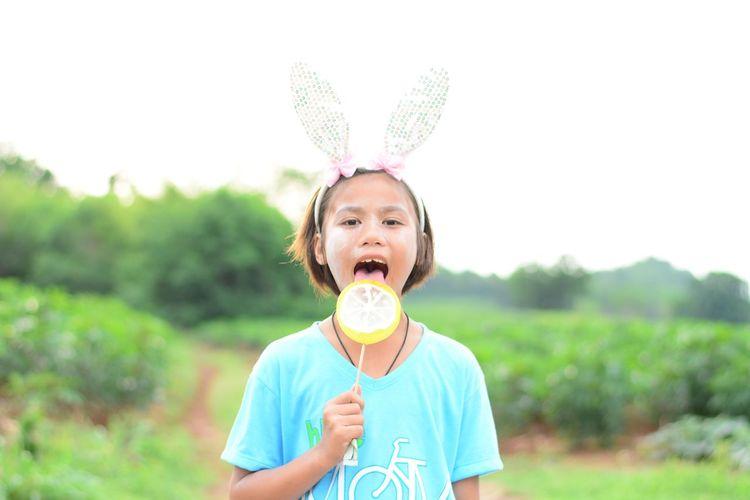Portrait of cute girl eating lollipop outdoors