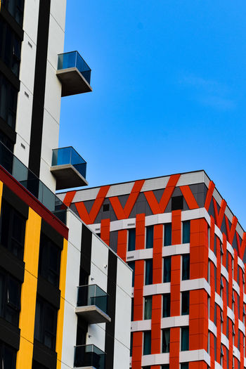 low angle view of office building against blue sky Aparment Architecture Blue Building Exterior Built Structure City Clear Sky Day Façade Glass And Stell Low Angle View Modern Modern Architecture No People Office Park Outdoors Primary Colors Red Residential Building Sky Skyscraper Window Yellow