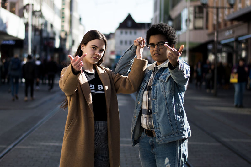 Portrait Of Couple Showing Middle Finger While Standing On City Street