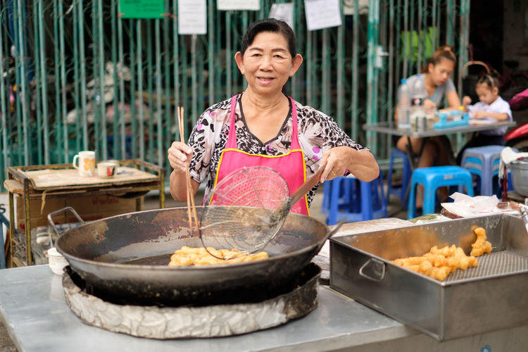Senior woman wearing apron preparing food at market stall