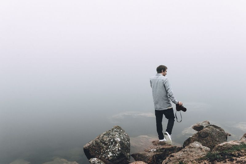 Rear view of mid adult man holding camera while standing on rock during foggy weather
