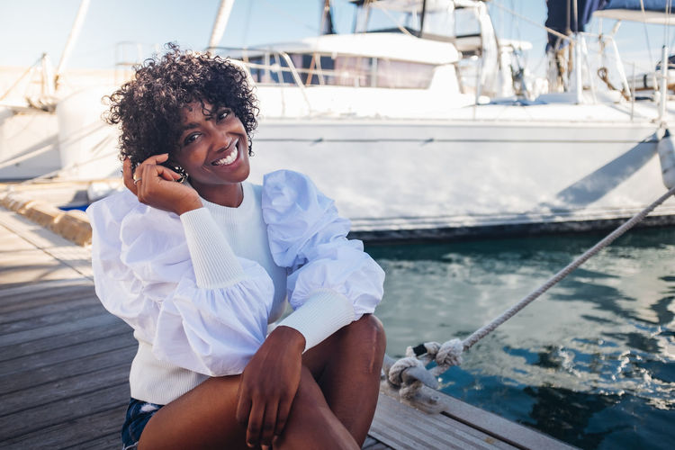 Smiling young woman using mobile phone in sea