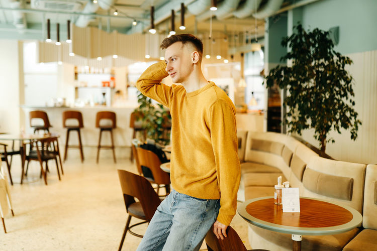Man looking away while sitting on table in cafe