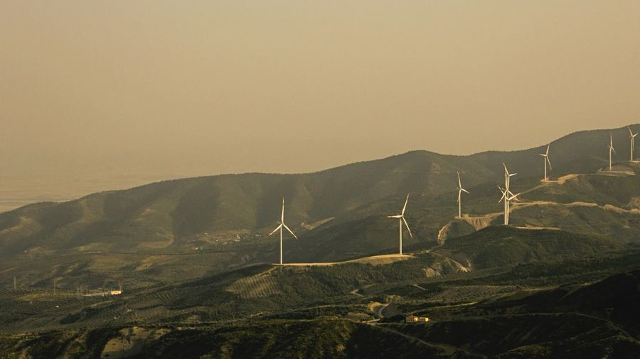 Scenic view of windmills on mountains against clear sky