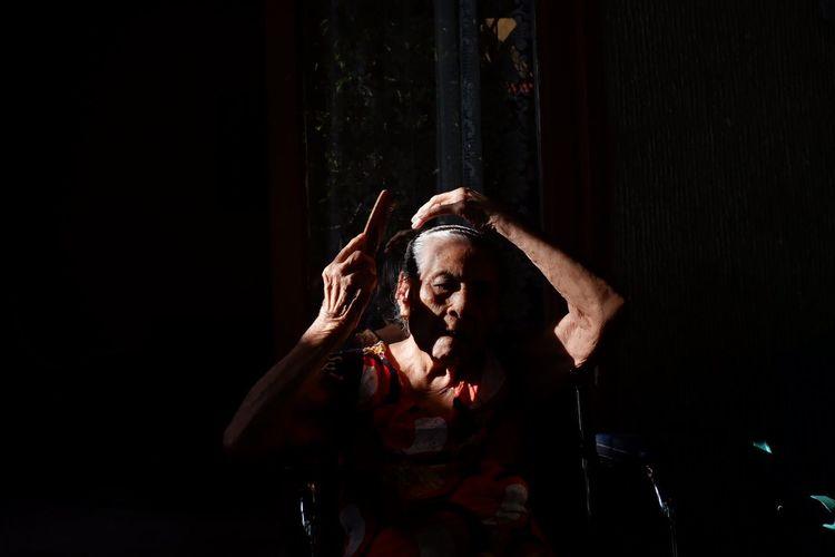 Senior woman combing hair while sitting in darkroom