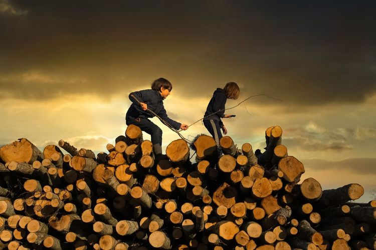 Two kids walking on log against sky during sunset