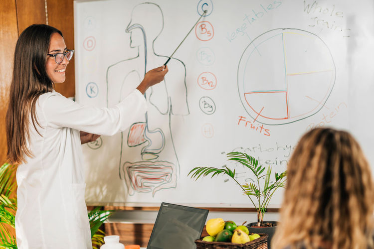 Female nutritionist, standing in front of a white board, explaining the importance of vitamin c