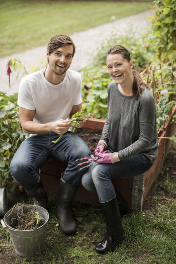 Portrait of smiling young couple sitting outdoors