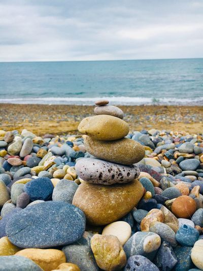 Stack of pebbles at beach against sky