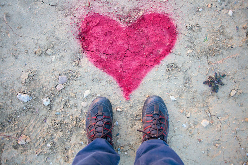 Low section of man standing by heart shape on street