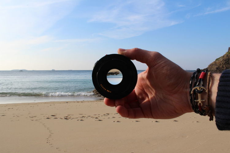 Close-Up Of Hand Holding Camera Lens At Beach Against Sky