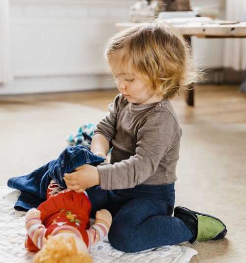 Cute Baby Girl Playing With Doll At Home