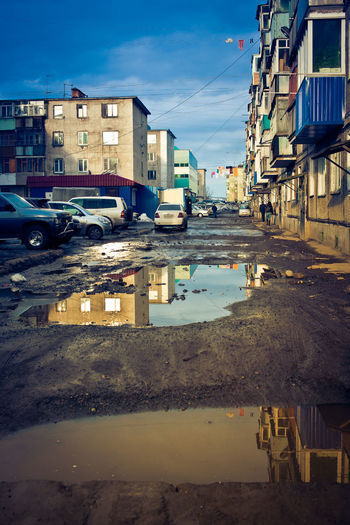 Reflection of building in puddle on road against buildings in city