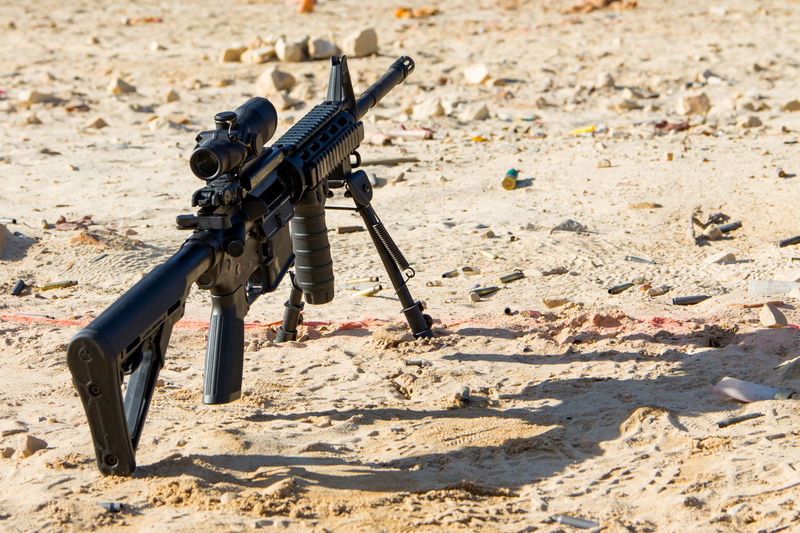 An AR-15 sits on the sandy, casing scattered ground behind the firing line at an outdoor range Ar-15 Ar15 Casings Day Defense Firearm Gun Machinery Military No People Outdoors Range Rifle Rocks Sand Scope Semi-automatic Shell Casings Shooting Sport Sunlight Tactical Target Shooting Weapon EyeEmNewHere