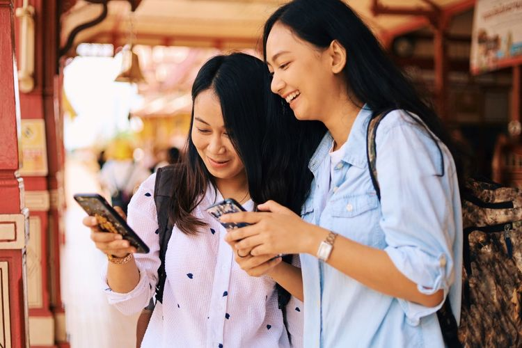 Young Adult Young Women Mobile Phone Wireless Technology Two People Focus On Foreground Smart Phone Leisure Activity Togetherness Long Hair Women Hair Real People Adult Communication Using Phone Holding Standing Waist Up Black Hair Hairstyle Outdoors