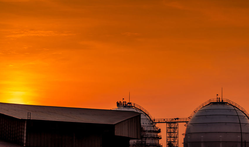 Industrial gas storage tank. lng or liquefied natural gas storage tank. red and orange sunset sky.