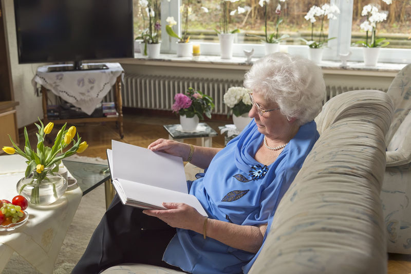 Older lady sits in her living room and reads an Book At Home Copy Space Couch Reads Relaxing Authentically Blue Clothes Book Comfortably Education Eighty Year Old Entertainment Flat Home Interior Look Old Woman Reading Help Rest Senior Senior Adult Sitting Sitting Room Sofa Text Size White Hair
