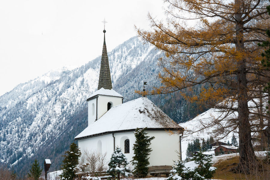wintertime alpine landscape with church Cold Temperature Snow Winter Tree Built Structure Architecture Building Religion Place Of Worship Belief Plant Building Exterior Spirituality Day Nature Mountain No People Outdoors Spire  Snowcapped Mountain Church Architecture Church Tower