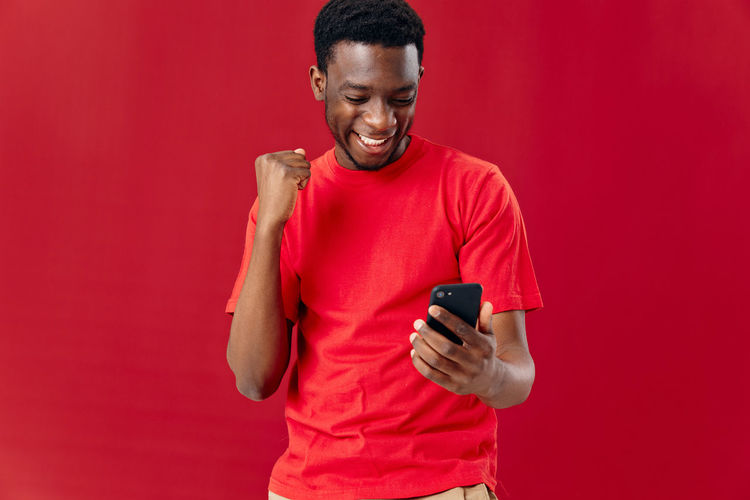 Smiling man using mobile phone against red background