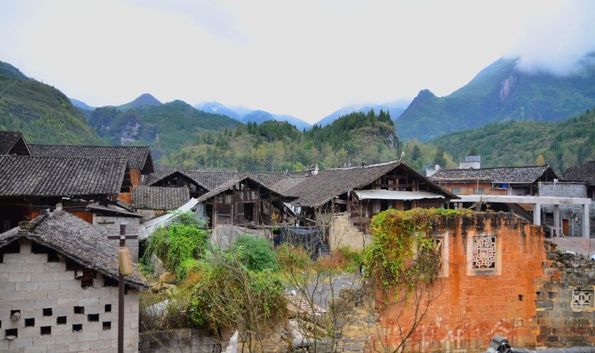 Houses by townscape against mountains