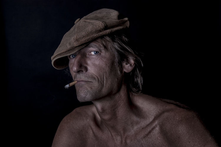 Hat Looking At Camera Adult Adults Only Black Background Close-up Headshot Indoors  Low Key Lighting Low Key Photography Mature Adult Older Man One Man Only One Person Only Men People Portrait Real People Rinkles Shirtless Sigarette Studio Shot