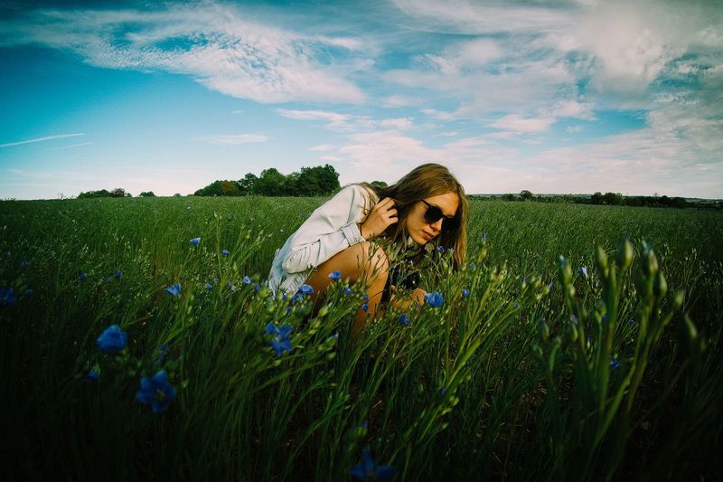 Young woman in sunflower field against sky