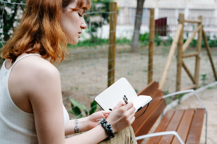 Side view of young woman reading book