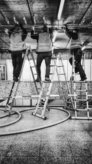 Three worker adjusting cable on ceiling