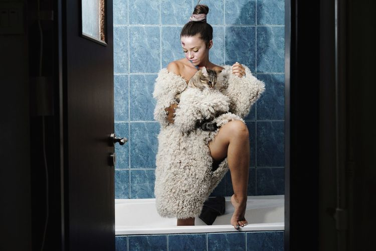 Woman wearing warm clothing while holding cat in bathtub
