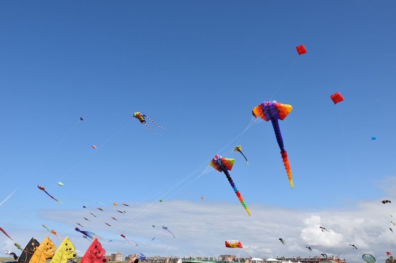 Low angle view of kites against blue sky