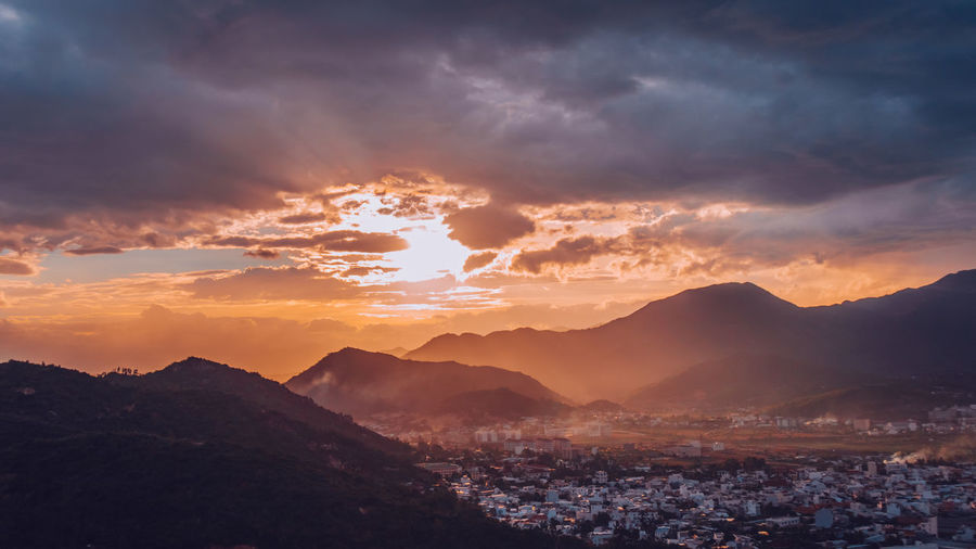 Scenic View Of Mountains Against Dramatic Sky During Sunset