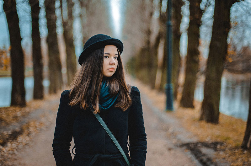 Portrait of beautiful young woman standing on land