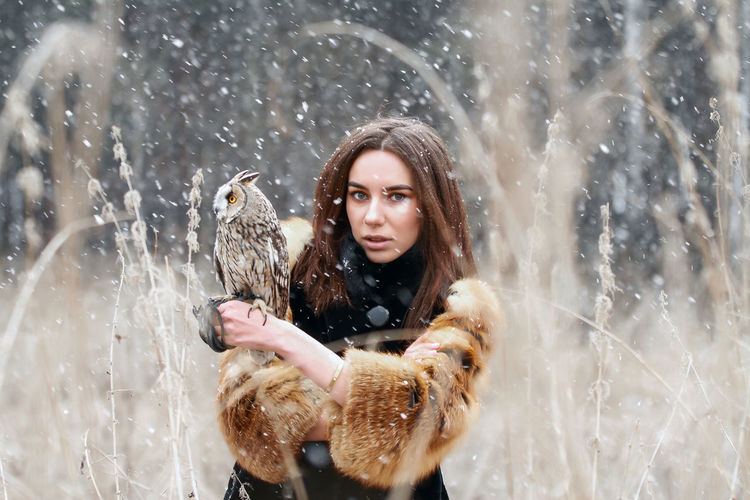 Portrait of beautiful young woman with owl outdoors