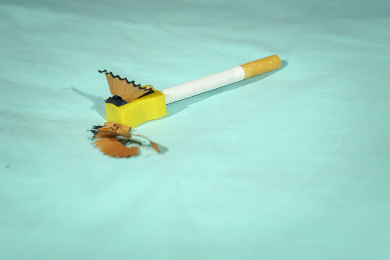 Close-up of yellow cigarette on table