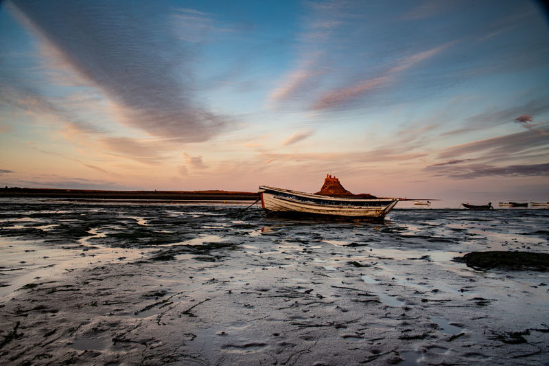 Boat on beach against sky during sunset