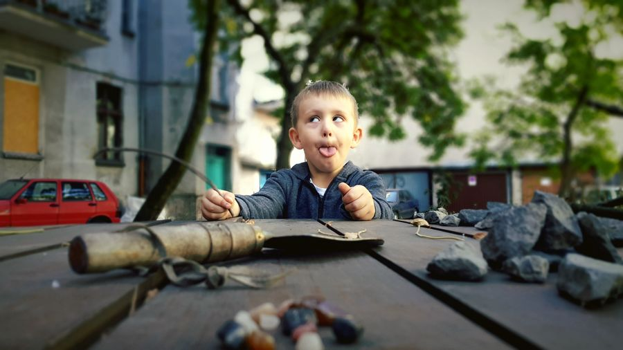 Cute Boy Making A Face By Table In City