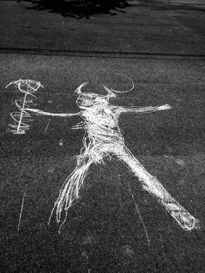 Chalk drawing of devil on asphalt