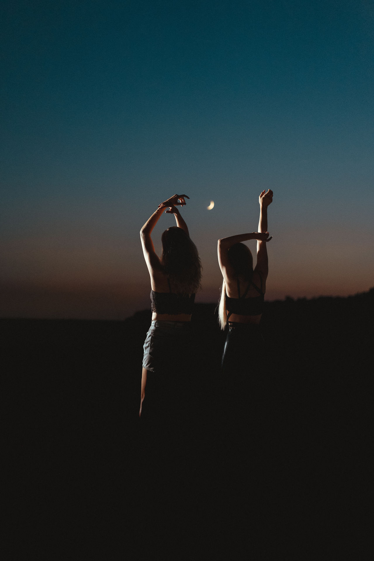Silhouette women with arms raised against sky during dusk
