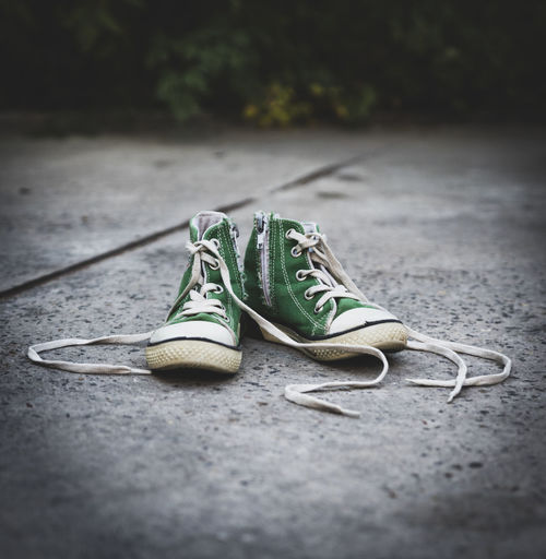 Close-up of green shoes on footpath