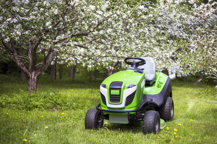 Riding mower, mowing grass in yard, tractor. Apple tree, bloom, garden. Backyard Blooming Countryside Countyside Cutter Garden Gardening Grass Home Homestead Lawn Lawn Cutter Lawn Cutting Lawnmower Mower Mowing Mowing The Lawn Mowing Tractor Nature Nobody Riding Tractor Spring Tractor