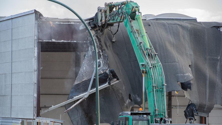 Excavator demolishing factory against sky