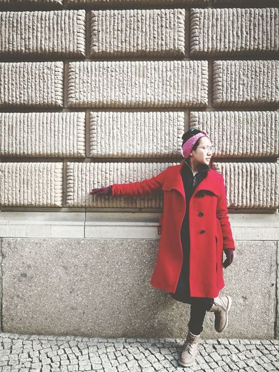 Full Length Of Woman Wearing Winter Coat While Standing Against Patterned Wall