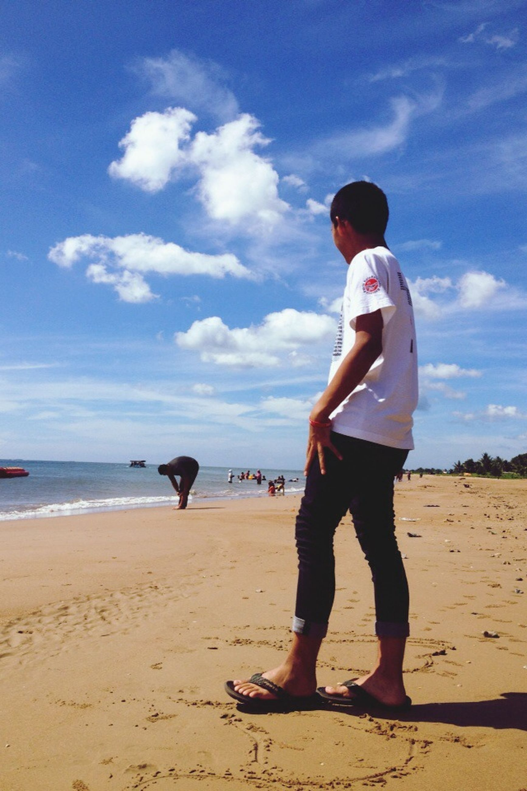 beach, full length, sky, sea, shore, sand, lifestyles, leisure activity, casual clothing, water, childhood, horizon over water, cloud - sky, rear view, standing, vacations, cloud, boys