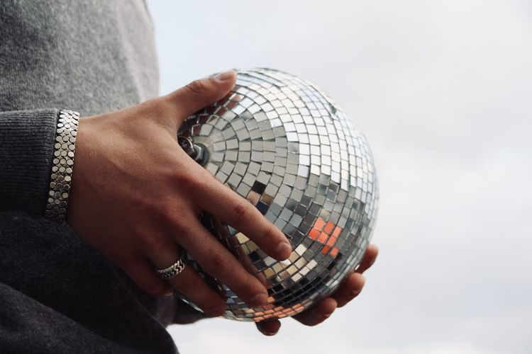 Midsection of man holding disco ball
