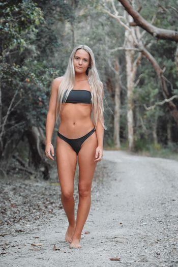 Portrait of beautiful bikini woman walking on dirt road