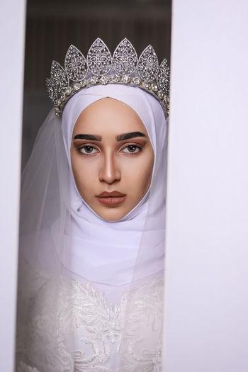 Portrait of young bride looking away through door