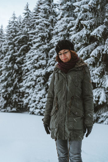 Young woman standing against trees during winter