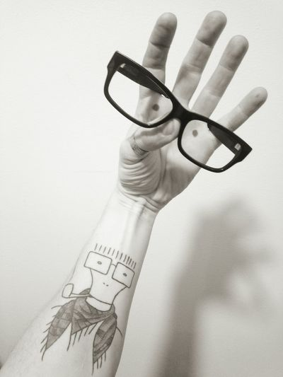 Close-Up Of Human Hand With Tattoo Holding Eyeglasses Against Wall