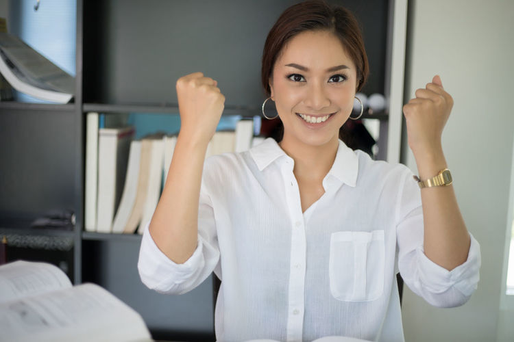 Portrait Of Smiling Young Businesswoman Clenching Fist At Office