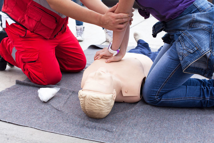 Instructor guiding woman to perform cpr on dummy